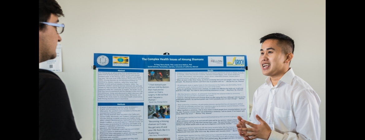 student presenting poster at annual symposium